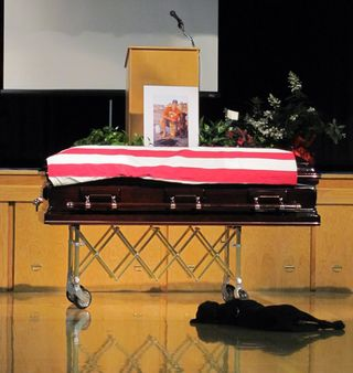 Labrador-retriever-hawkeye-lays-by-the-casket-during-the-funeral-of-his-owner-navy-seal-jon-tumilson-pic-getty-images-681846102